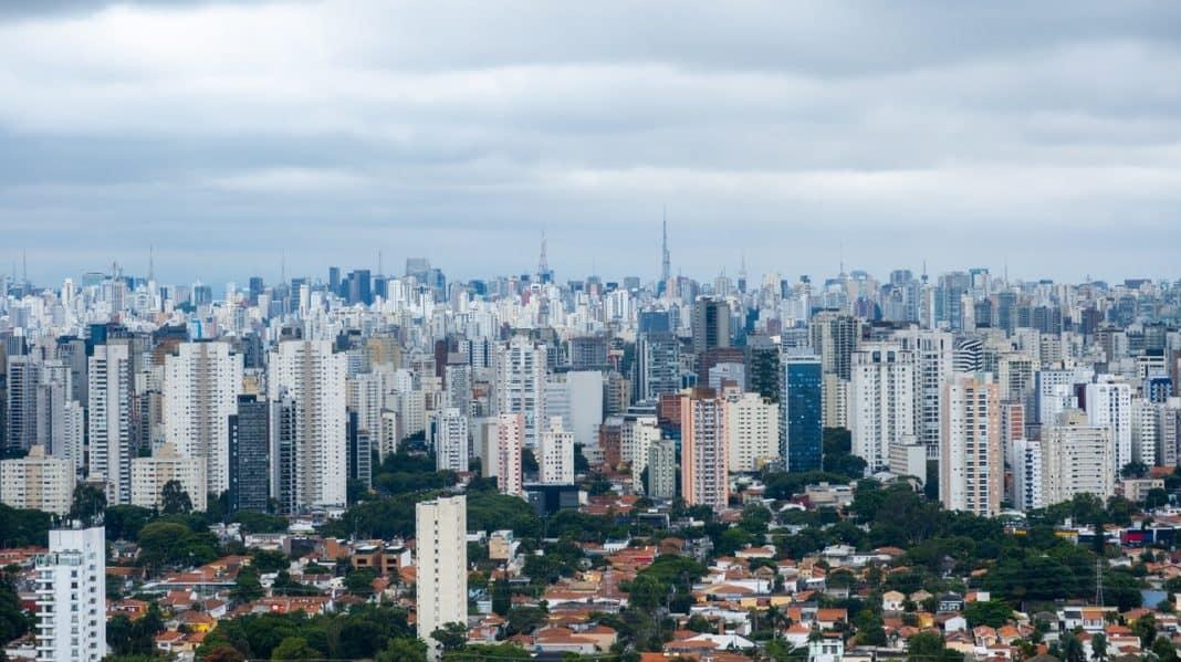Fotografia de uma metrópole com prédios, casas e vegetação. O céu está um pouco nublado.