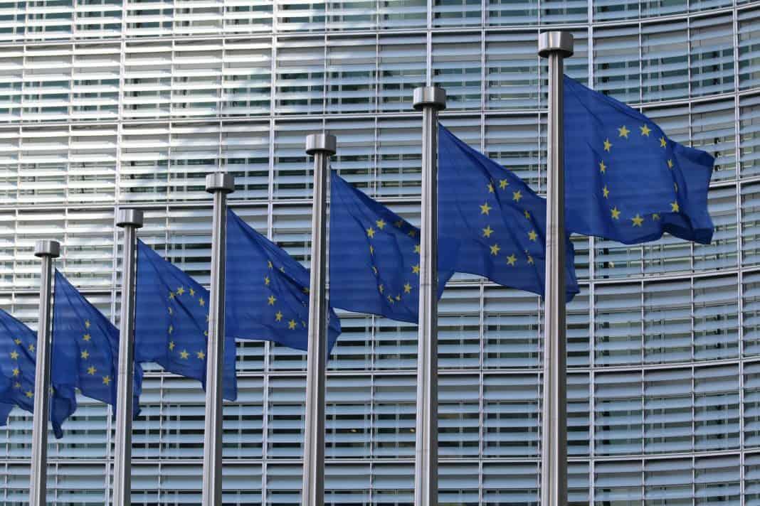 Fotografia de diversas Bandeiras da União Europeia, com um prédio ao fundo.