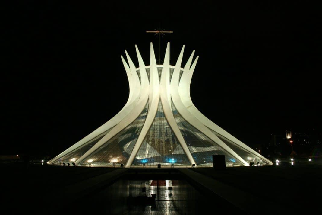 Fotografia da Catedral de Brasília durante a noite, iluminada por feixes de luz em sua base.