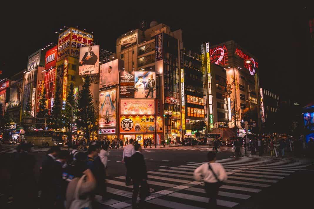 fotografia da cidade de Tóquio durante a noite. É possível visualizar prédios com diferentes outdoors no fundo da imagem, sendo que a frente pessoas cruzam uma faixa de pedestres.