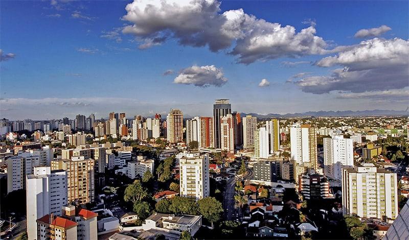 Vista panorâmica da cidade de São Caetano do Sul. O céu está com poucas nuvens, o dia está ensolarado e é possível ver prédios e casas se expandindo até o horizonte da cidade.
