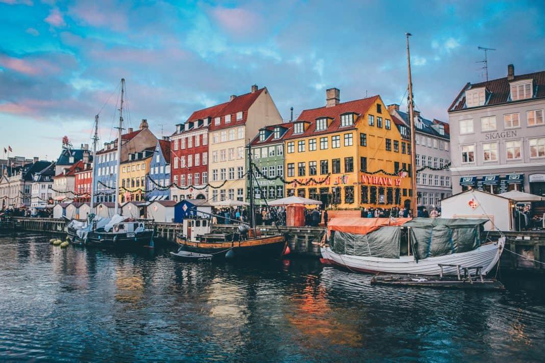 Fotografia da cidade de Copenhage, na qual é possível ver três barcos parados próximos a casas coloridas.