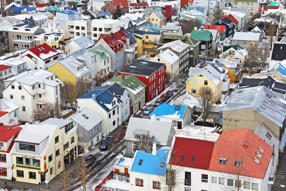 Fotografia aérea de um bairro localizado na capital da Islândia, Reykjavik, composto por casas coloridas com os telhados cobertos de neve.
