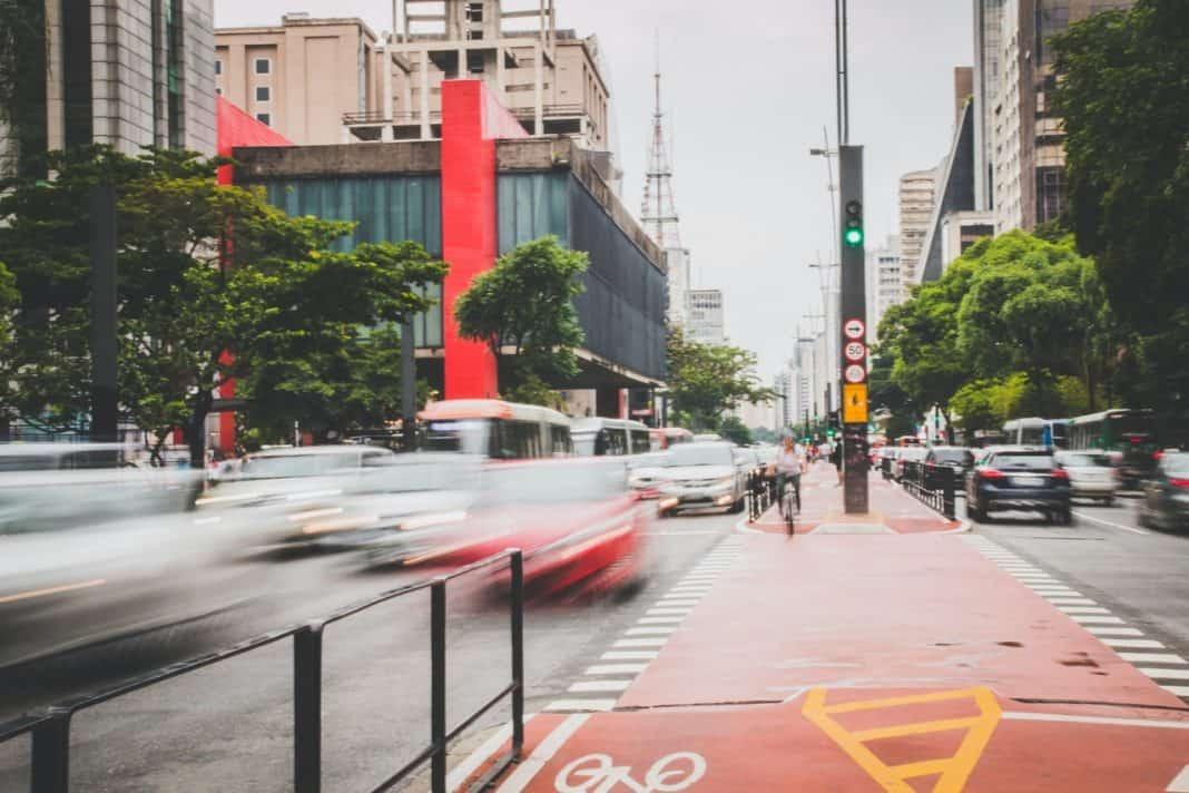 Fotografia da Avenida Paulista, em São Paulo, na altura do Masp, com circulação de veículos, pessoas andando de bicicleta na ciclovia, bem como edifícios e árvores
