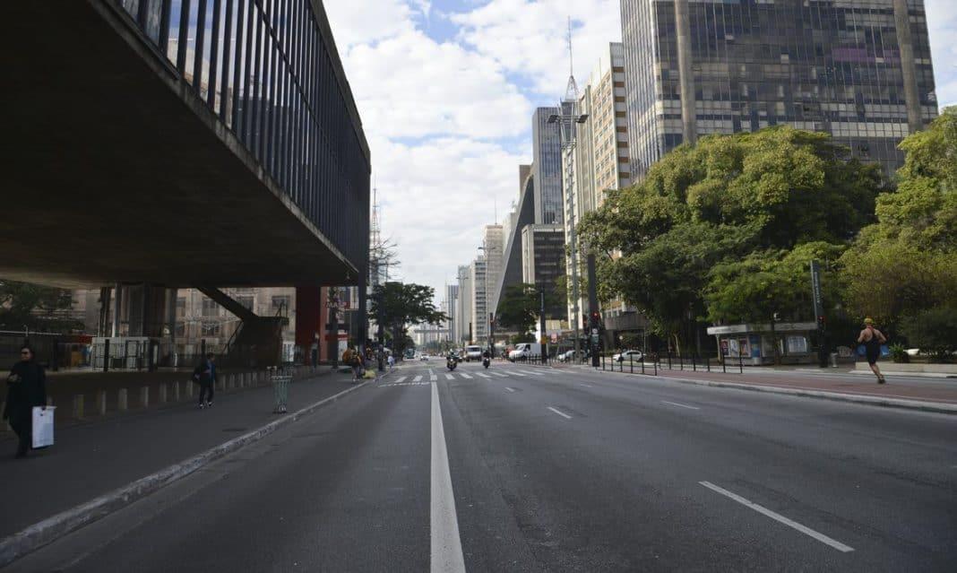 Foto da Avenida Paulista, em São Paulo, na altura do Masp, com a via com pouco movimento e enfatizando a calçada, o canteiro central e as árvores, com movimento de carros, motos e pedestres