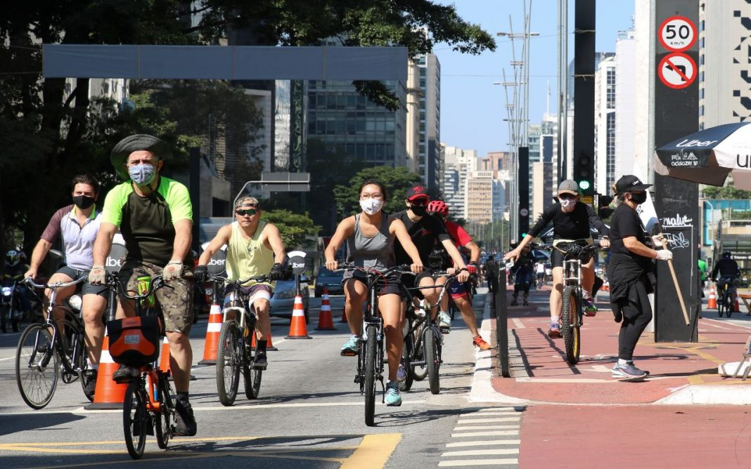 Foatografia de usuários, homens e mulheres, andando de bicicleta em ciclovia de avenida movimentada, em meio aos edifícios e também um pouco paisagismo, com algumas árvores