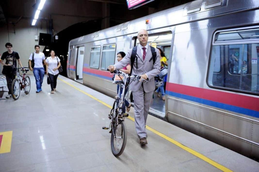 Fotografia de homem na plataforma saindo do vagão do metrô e com bicicleta, com mais usuário ao fundo e um deles também de bicicleta