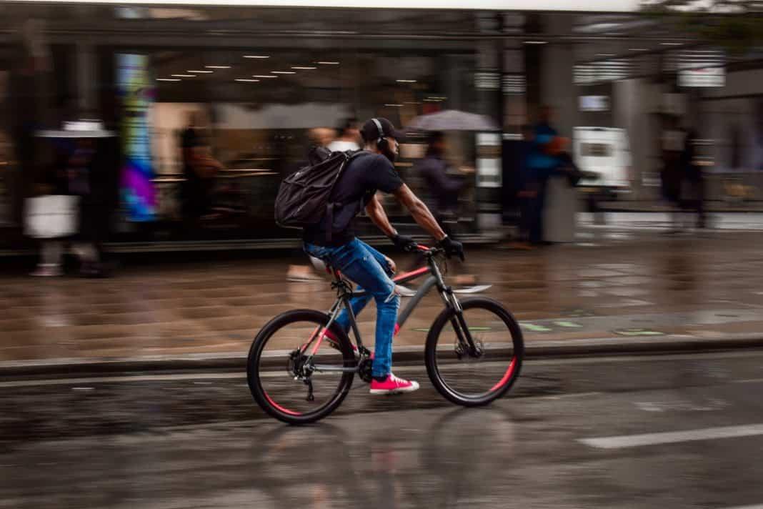 Fotografia de homem jovem se locomvendo na cidade debicicleta