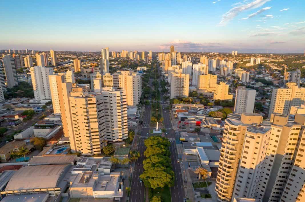 Fotografia vista da cidade de Campo Grande, Mato Grosso do Sul, com visão dos edifícios, avenidas e residências. O céu está azul