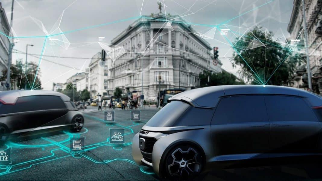 Fotografia/reprodução de ambiente urbano moderno inteligente com veículos autônomos, por meio de representação gráfica de inteligência artificial, nas cores verde e branco. Os carros se conectam aos demais sistemas de mobilidade urbana. Ao fundo, movimentação de pessoas, edifícios e um pouco de paisagismo