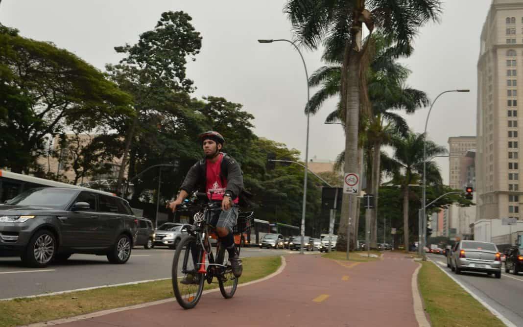 Fotografia de ciclovia na Avenida Brigadeiro Faria Lima, região oeste de São Paulo, com um usuário de bicicleta, onde se destacam a paisagem verde, edifícios e a movimentação de veículos