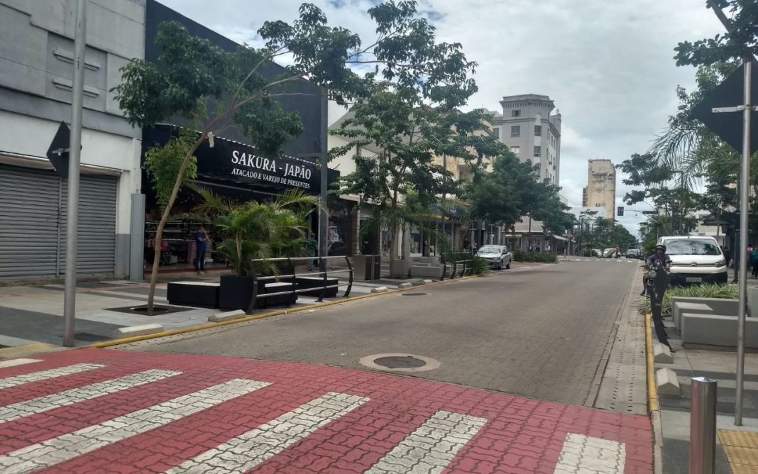 Fotografoa de avenida de comércio revitalizada, no centro de Campo Grande, com faixa acessível para pedestre, arborização, indivíduo de moto e veículos estacionados