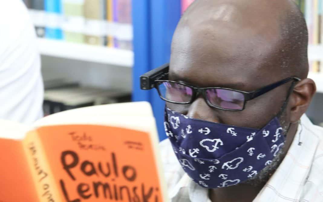 Fotografia de homem lendo livro de Paulo Leminski usando leitor digital com inteligência artificial, no projeto Fábricas de Cultura, do Governo do Estado de São Paulo