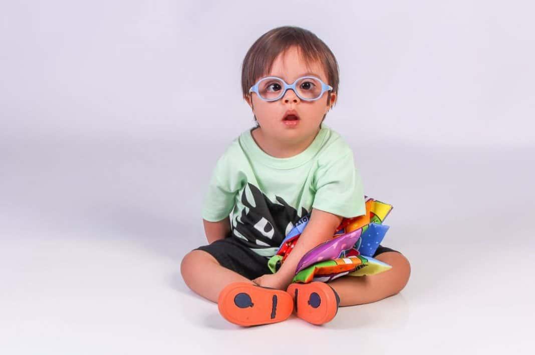 Criança durante ensaio fotográfico do projeto Galera do Click, realizado em 2020, para uma exposição sobre a síndrome de Down. Luis Fernando, 2 anos, na foto, sentado com um livro infantil colorido e roupa também colorida, nas cores verde e preto, tênis azul e laranja, e óculos azul