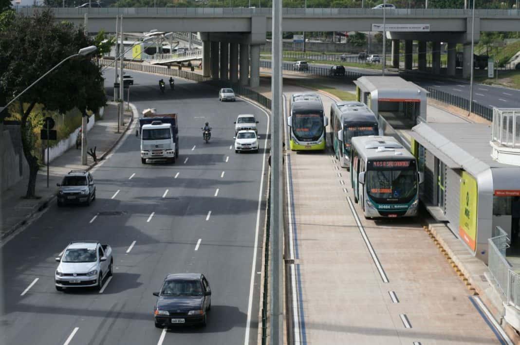 Fotografia de onibus coletivo em avenida na cidade, com veículos na faixa à esquerda