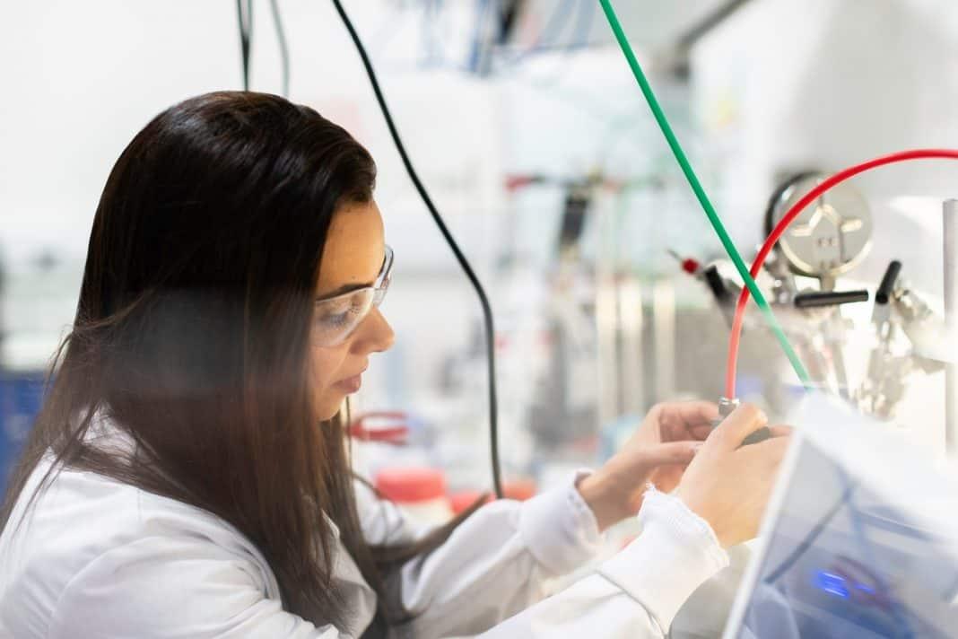Mulher em laboratório de inovação com óculos de proteção e jaleco