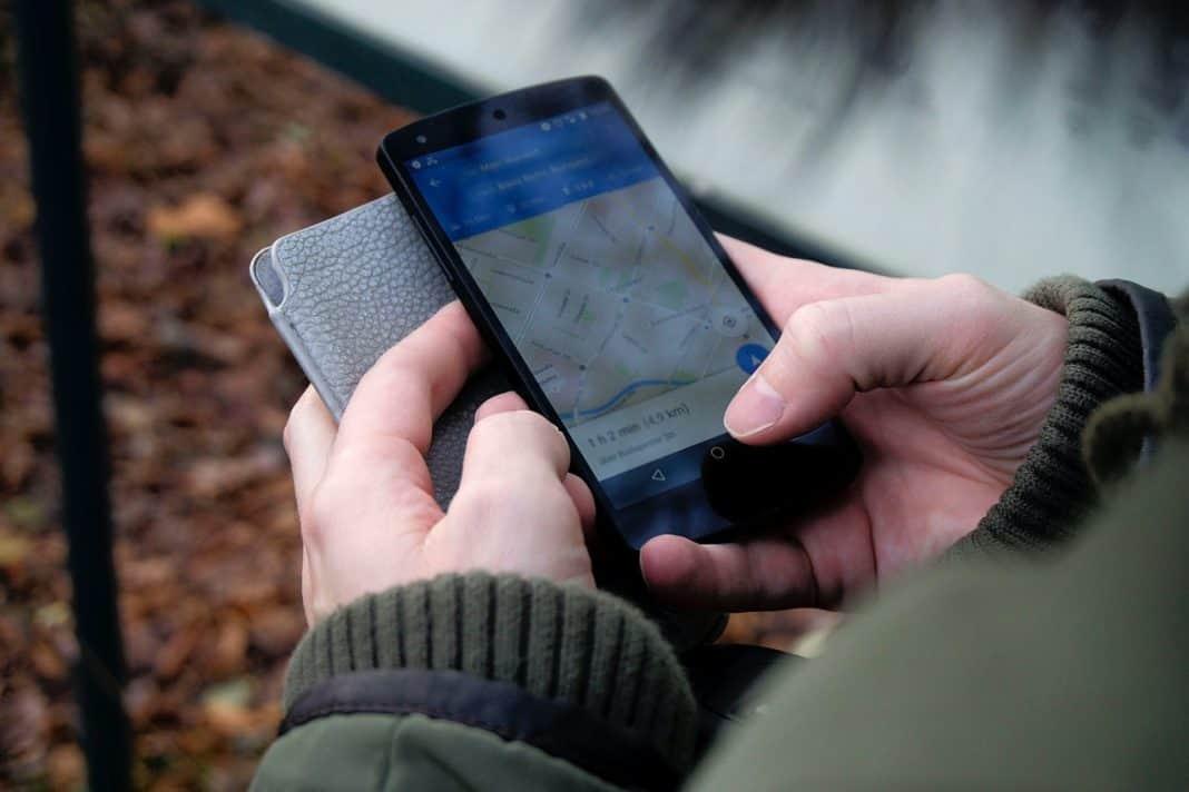 Fotografia da tela de um celular mostrando o mapa de localização de táxi de aplicativo, onde aparece o indivíduo segurando o aparelho e a capa do mesmo