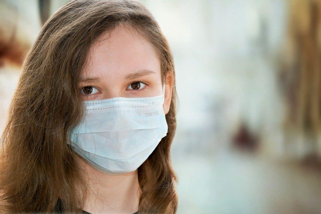 Fotografia de uma criança caucasiana de cabelos castanhos utilizando uma máscara de proteção ao coronavírus
