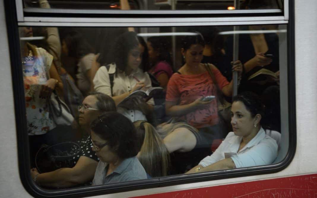 Fotografia de vagão de metrô ocupado por mulheres sentadas e em pé. Algumas mulheres estão lendo livros e outras acessando o celular
