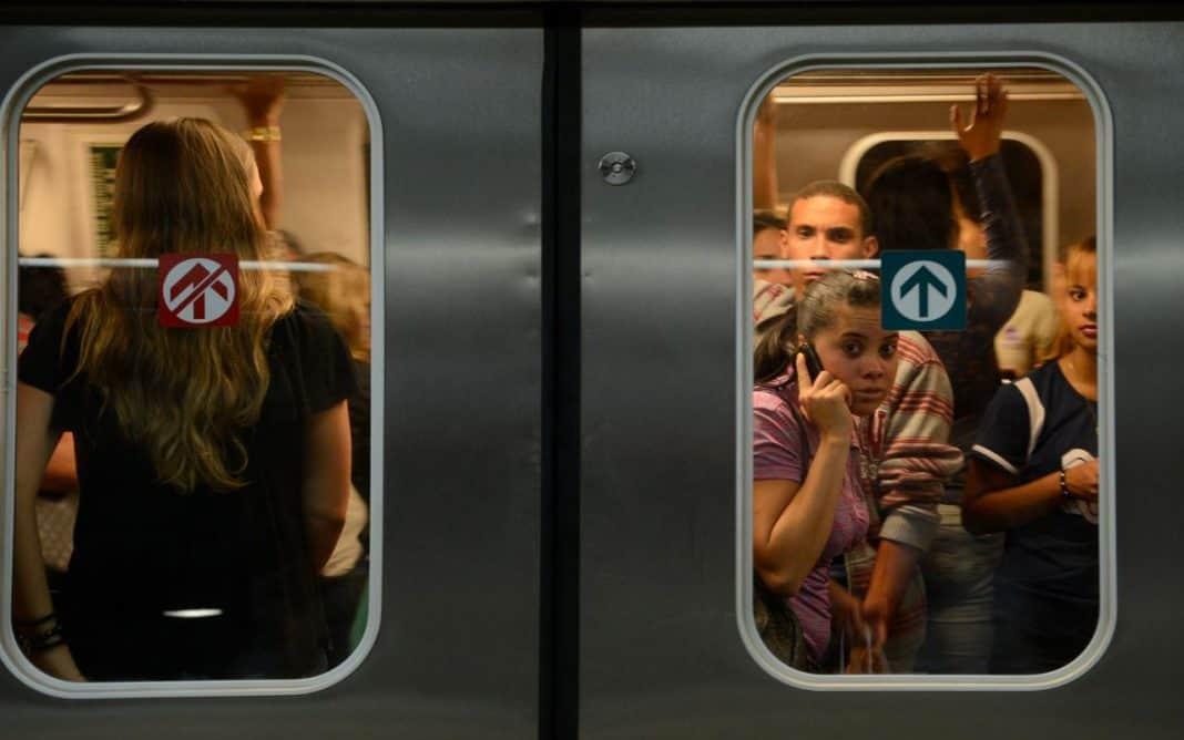 Fotografia de vagão de metrô cheio com as portas fechadas