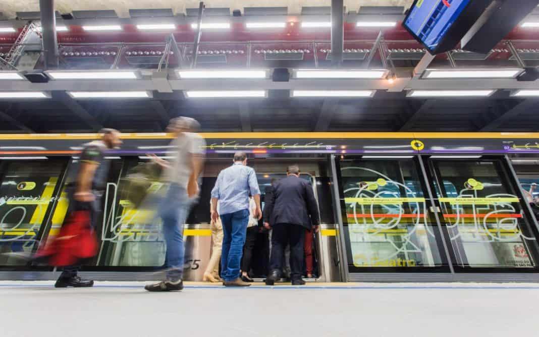 Fotografia de plataforma de embarque de metrô com passageiros entrando no vagão
