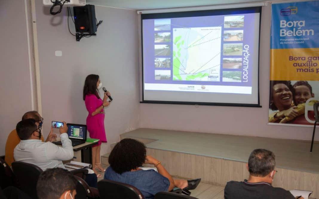 Fotografia da apresentação do projetos estruturantes de mobilidade da cidade de Belém, com uma mulher falando ao microfone fazendo referencia às imagens de slides no telão. Algumas pessoas na plateia acompanham a ação