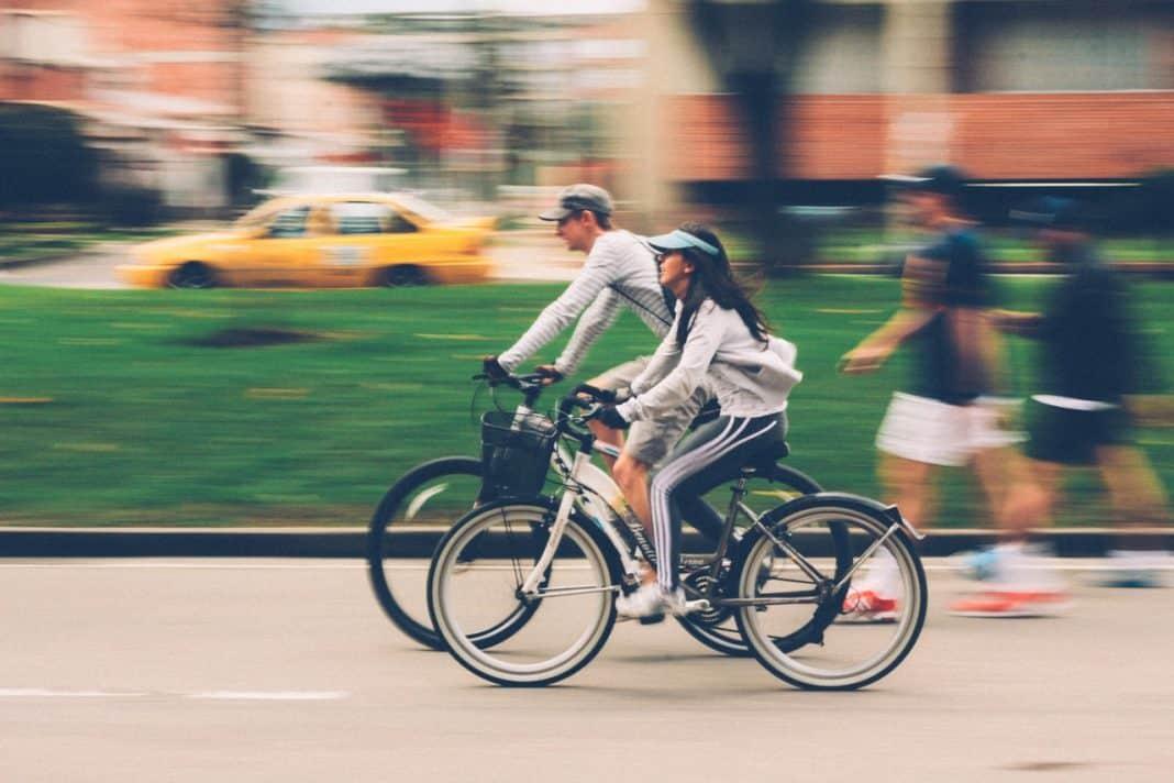 Fotografia de pessoas se locomovendo em centro urbano de bicicleta, caminhando e táxi, com área verde e, ao fundo, edificações
