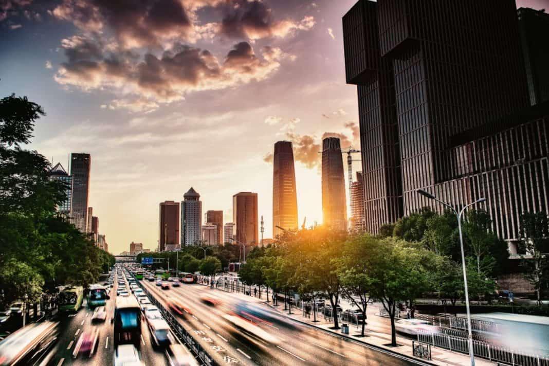 Fotografia de Avenida movimentada com várias algumas faixas, ciclofaixas e intensa movimentação de veículos em todos os sentidos. Altos e modernos edifícios, a presença de árvores e o sol do final do dia completam a paisagem