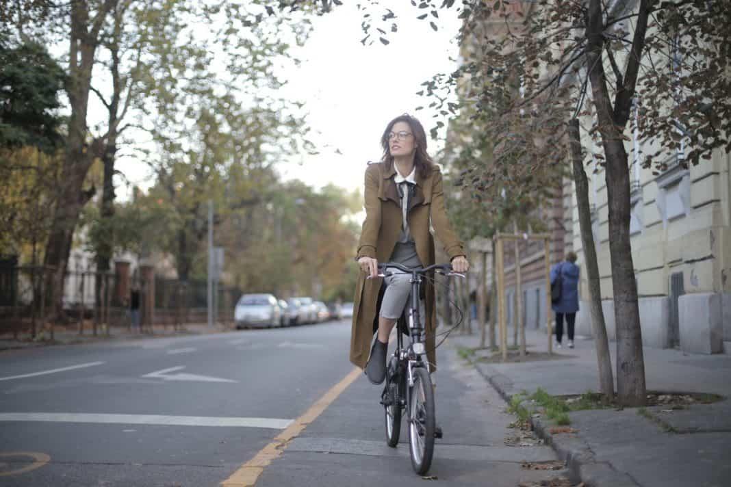 Fotografia de mulher se deslocando de bicicleta em cidade