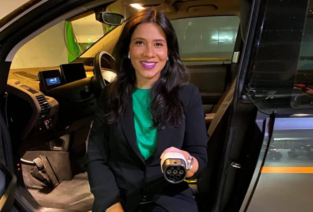 Fotografia de executiva sentada no banco de carro elétrico com as pernas para fora e segurando o carregador do veículo