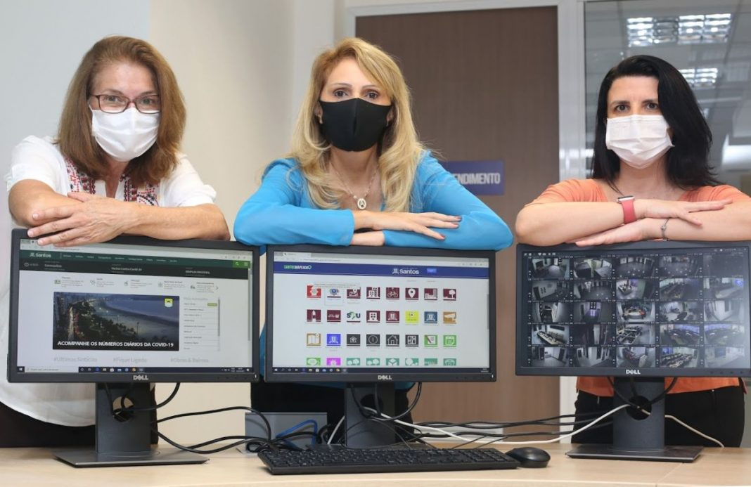 Fotografia de três mulheres da gestão do Departamento de Tecnologia da Informação da Prefeitura de Santos, São Paulo. Elas estão atrás de uma mesa com três computadores, que mostram imagens de monitoramento do município, e com os braços cruzados em cima dos mesmos