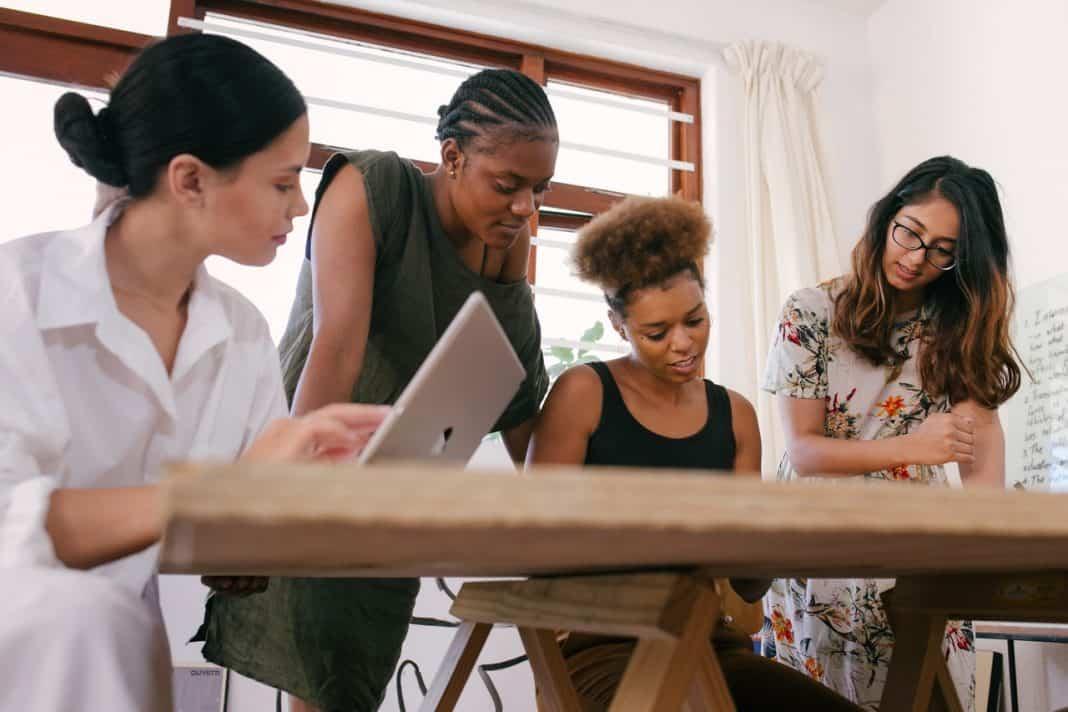 Mulheres em ambiente de escritório, com mesa e notebbok. Ambiente com janela e ampla acabamento madeira e cortina branca