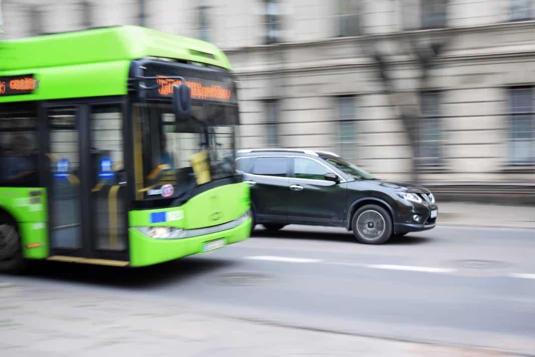 Fotografia de onibus elétrico em movimento na avenida e carro também