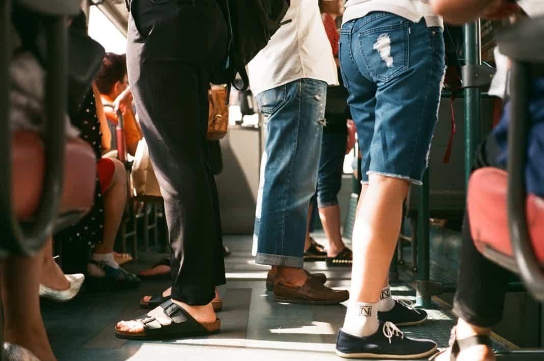 Fotografia de passageiros no ônibus. É possível visualizar apenas a cintura e pés dos passageiros.