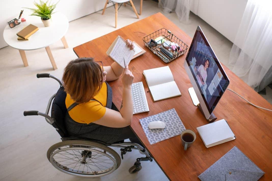 Fotografia de mulher com deficiência em cadeira de rodas em aula online
