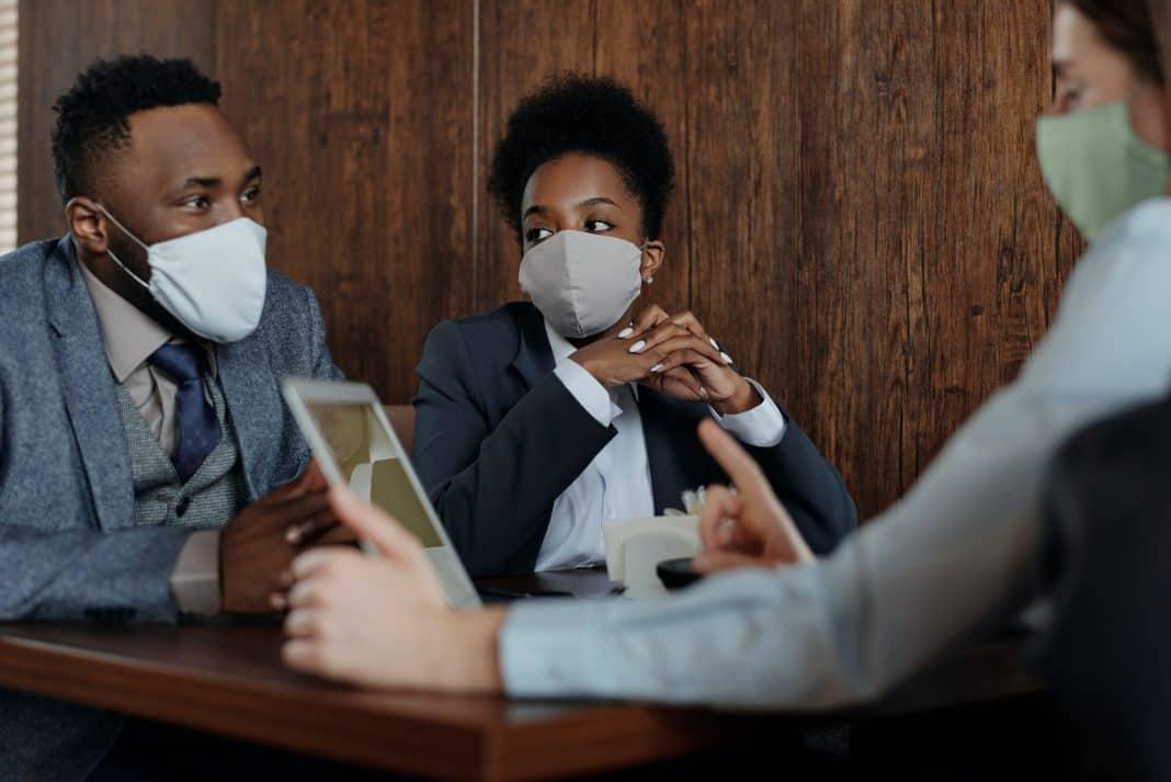 Fotografia de três pessoas em uma reunião utilizando máscaras de prevenção contra o coronavírus.