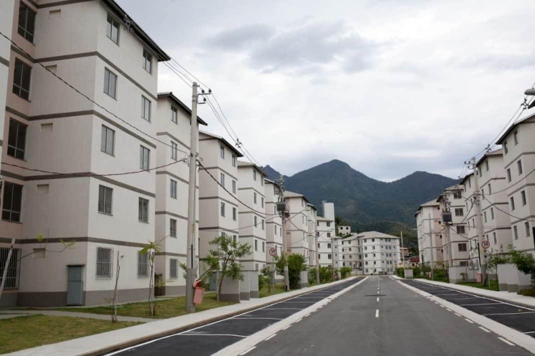 Fotografia de condomínio residencial de prédios de cinco andares. A construção popular planejada contempla urbanismo com gramado em volta dos edifícios, separados por uma rua, e algumas árvores em fase inicial de crescimento. Ao fundo, paisagem verde de serra e, também, vista do céu um pouco nublado