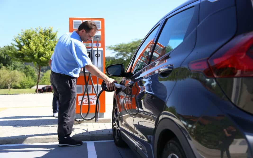 Homem em posto fazendo recarga de carro elétrico