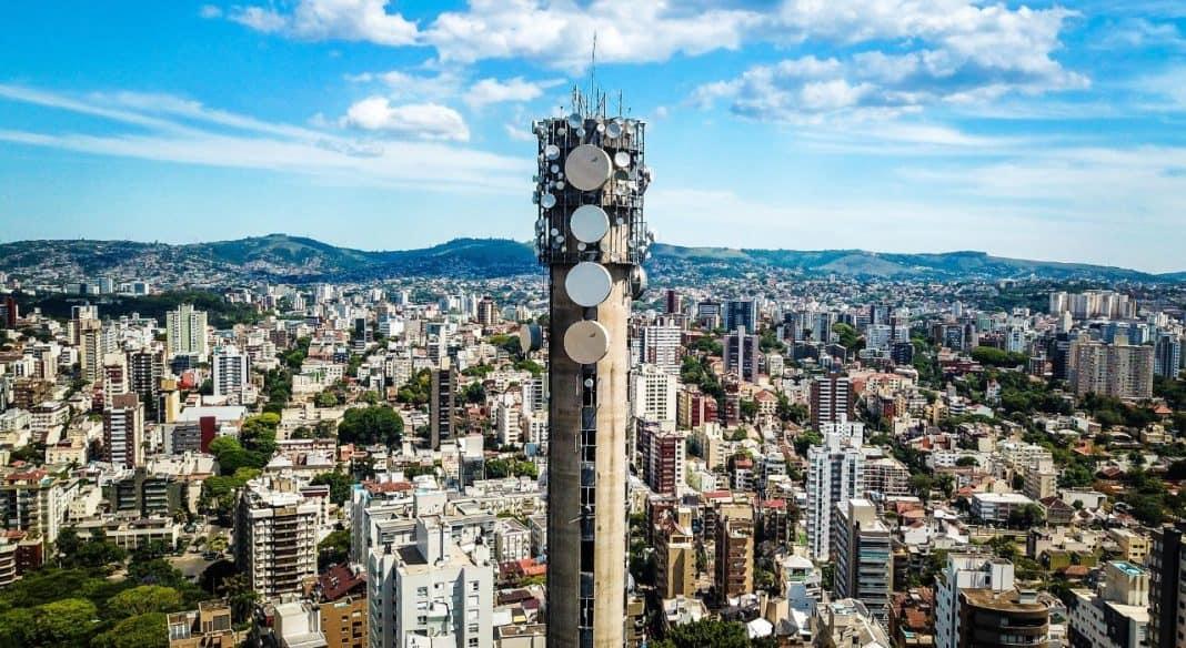 Fotografia de antena de telefonia com amplo cenário da cidade de Porto Alegre