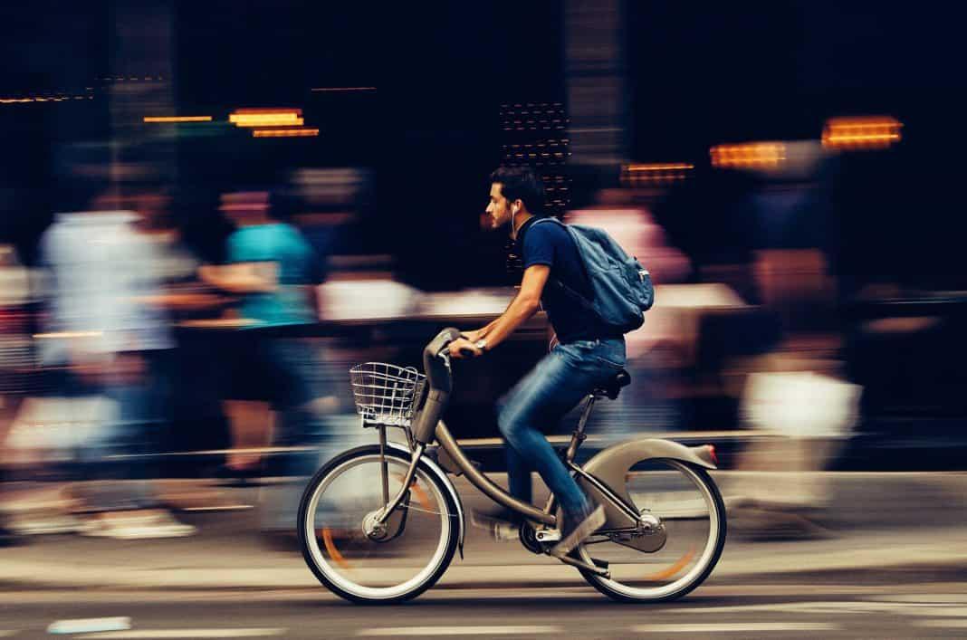 fotografia de um homem com uma mochila nas costas andando de bicicleta na rua.