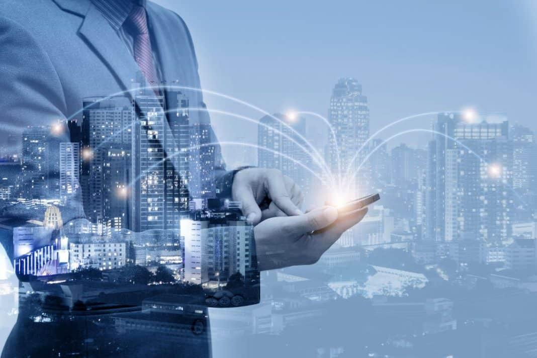 Reprodução de tecnologia conectada à cidade, com representação de homem utilizando tablet que interliga os vários sistemas