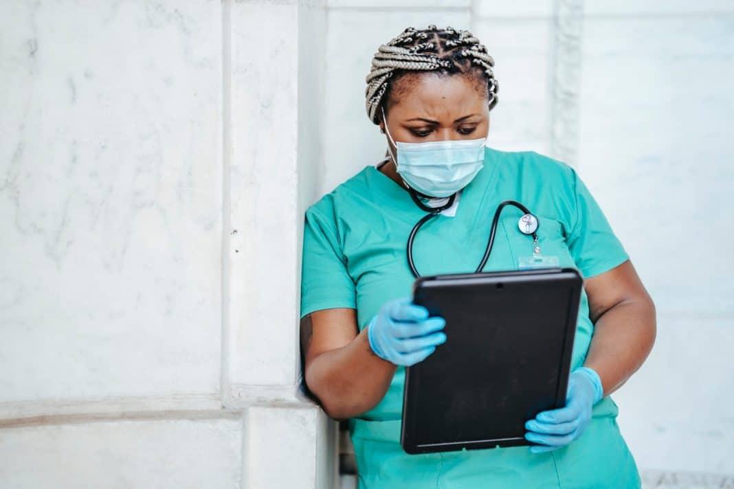Fotografia de fundo claro com profissional da saúde, com uniforme hospitalar verde, luvas azul e estetoscópio, em cena que remete à pandemia da covid-19. Com expressão de preocupação e usando máscara, ela está lendo e um tablet