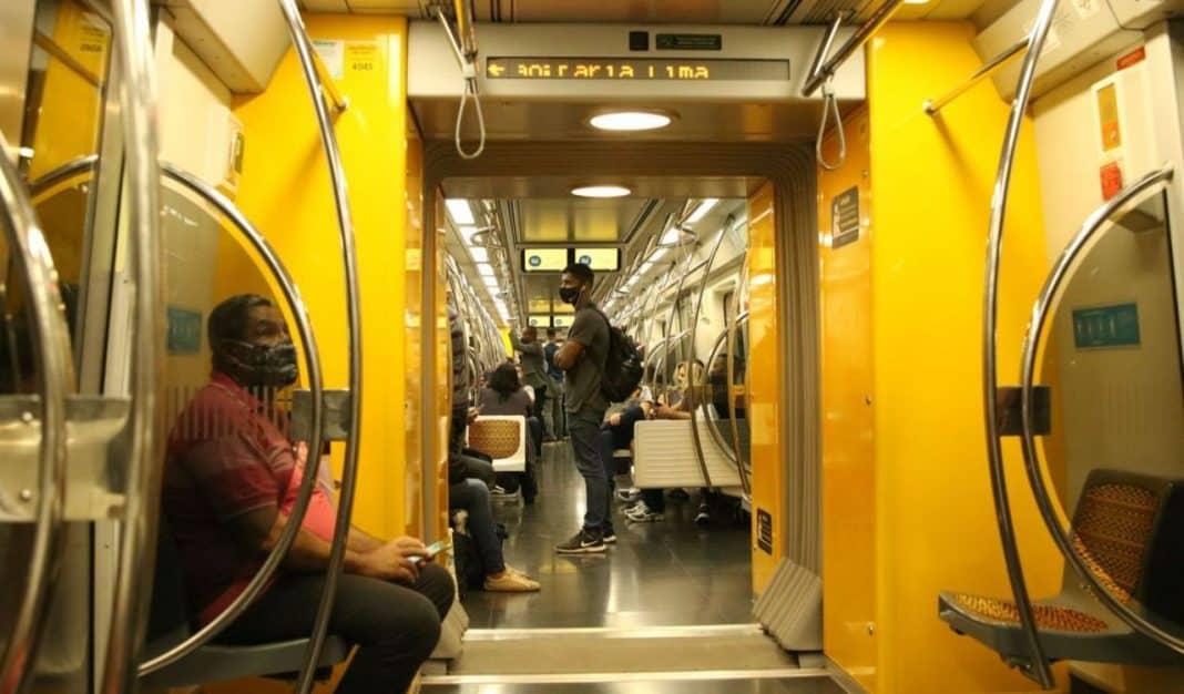 Fotografia da mobilidade urbana de vagão de metrô com passageiros em deslocamento. As pessoas usam máscara e estão sentadas e em pé
