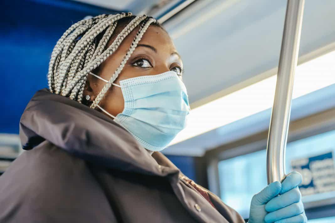 Fotografia de uma mulher negra em um ônibus utilizando máscara e luvas azuis como forma de proteção ao coronavírus