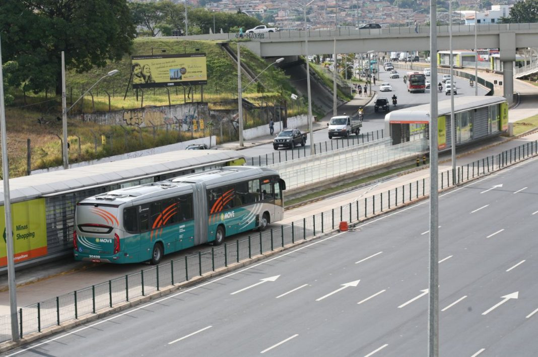 Fotografia de ônibus coletivo em avenida na cidade, com veículos na faixa também