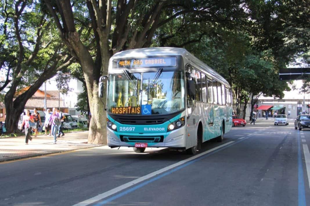 Fotografia de Avenida arborizada em dia ensolarado, com movimentação de pessoas na calçada, ônibus de transporte público de passageiros na faixa dedicada e carros no segundo plano