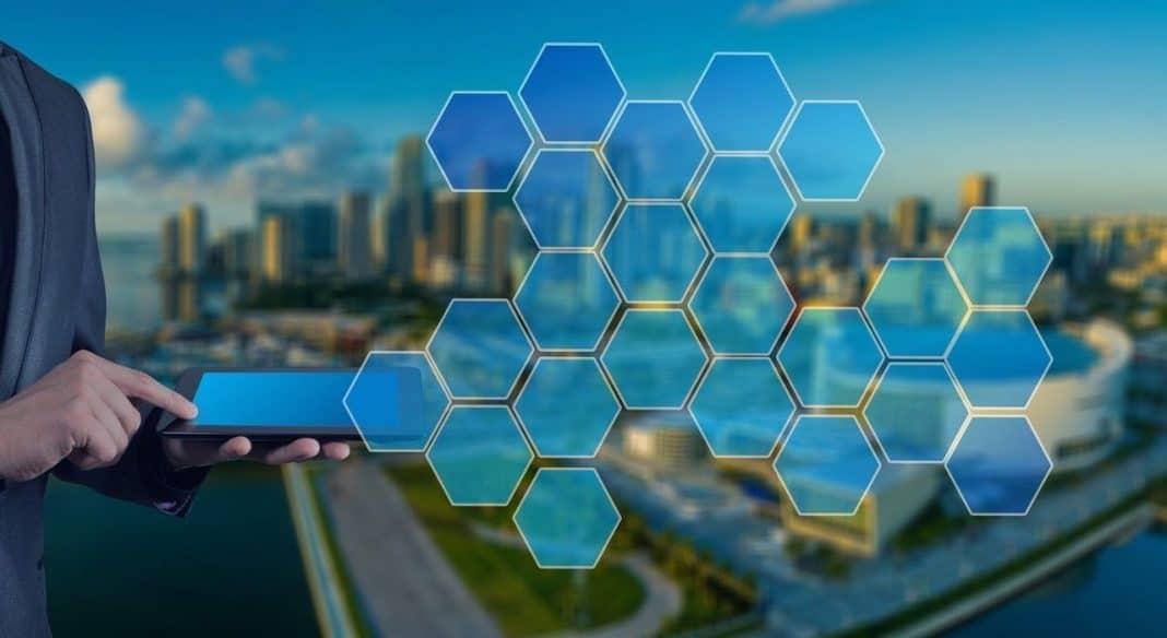 Fotografia e smart cities com representação de homem utilizando tablet e fazendo conexão das tecnologias com a cidade, que está em segundo plano