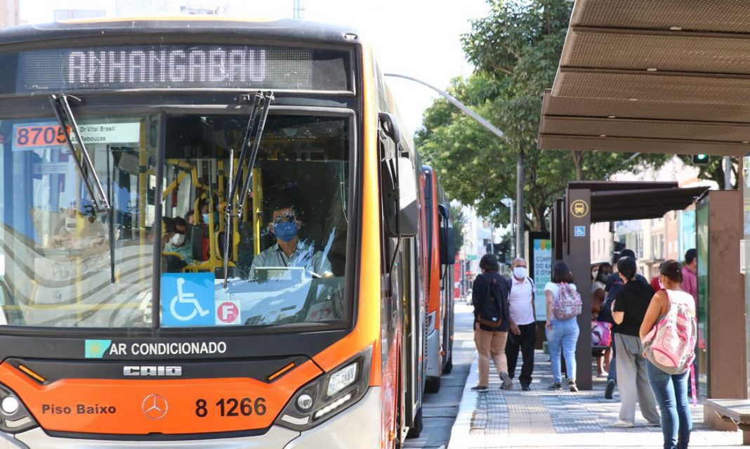 Foto de transporte público em dia ensolarado e em região urbana, com ônibus coletivo parado em ponto de embarque de passageiros. Local concentra pessoas sentadas e em pé e estas usam máscara