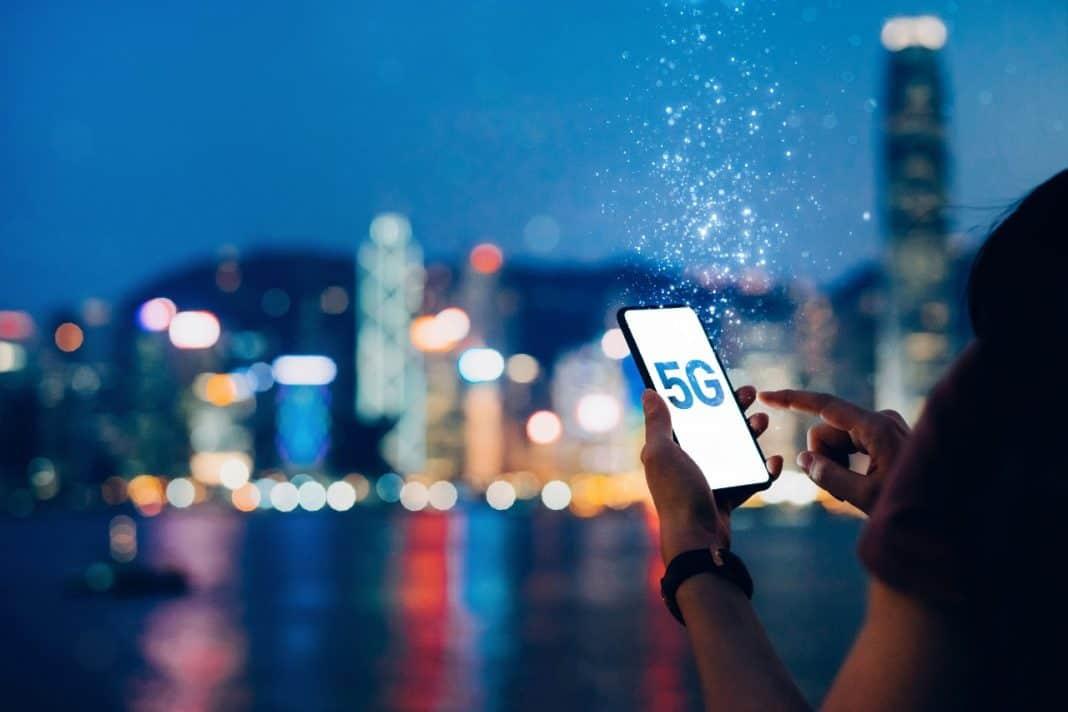Fotografia de indivíduo tocando a tela de um celular com a marca 5G e, ao fundo, com pouca nitidez o contorno de uma cidade, com bastante colorido e predominância do azul, bem como pontos laranja, vermelho, amarelo e branco. A presença da pessoa de costas, no primeiro plano, é por meio das mãos e ombro esquerdo. A imagem sintetiza a tecnologia 5G e as cidades inteligentes
