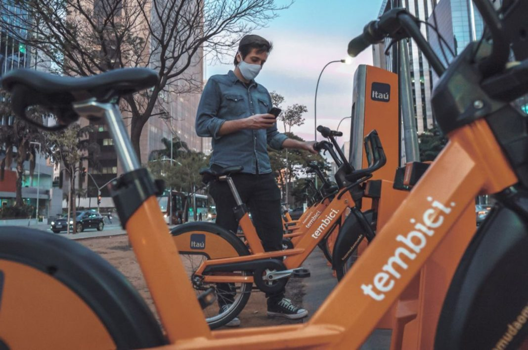 Fotografica de homem jovem usando a tecnologia do celular em bicicletas compartilhadas